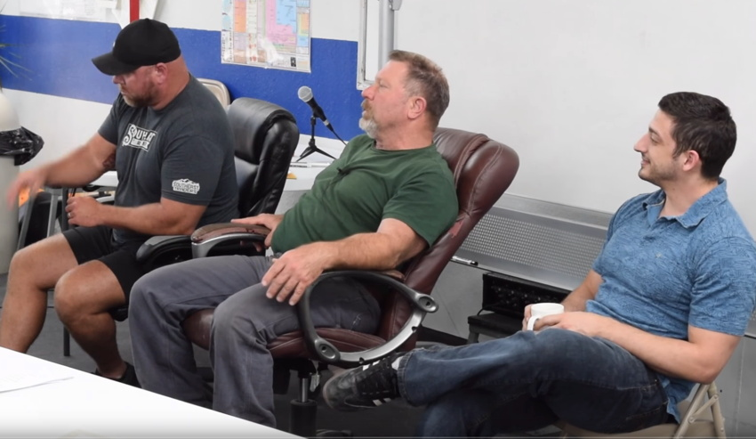 Somewhat overweight 59-year-old with cinnamon beard seated between classic meathead and slim Greek