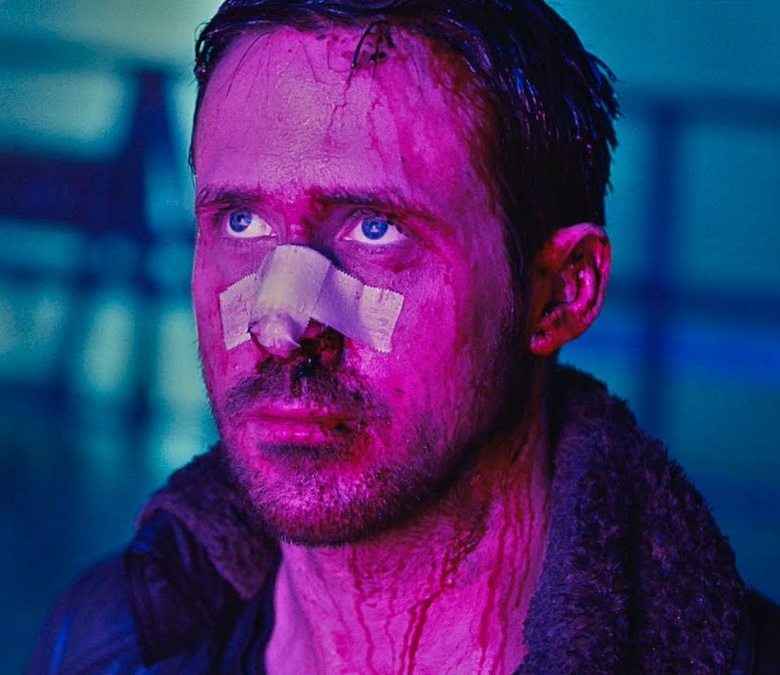 Ryan Gosling in 'Blade Runner 2049': blue background, deep magenta hue on his face, bandage across his nose, blue eyes upturned