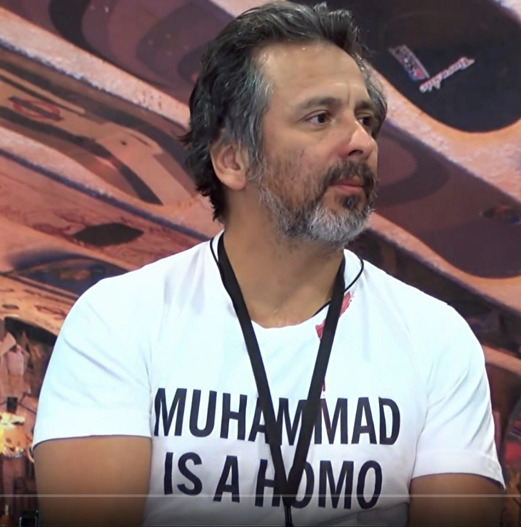 Somewhat-grey-haired Hispanic in MUHAMMAD IS A HOMO T‑shirt