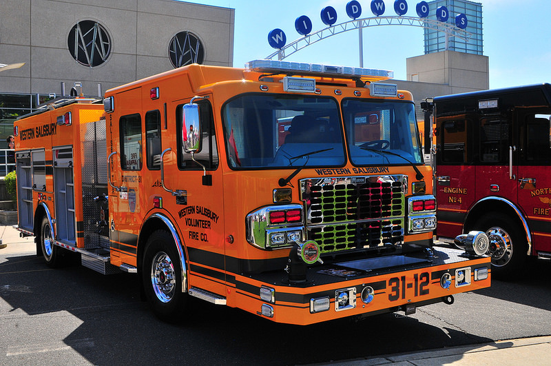 In strong sunshine, luminous orange firetruck sits parked, with lime-green reflection on grille, industrial type in black