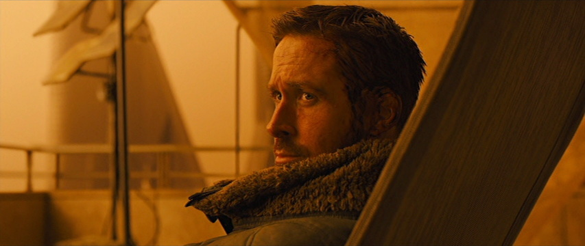 Amber-tinted scene shows R. Gosling turning his head to the left, tall fur-like collar folded slightly