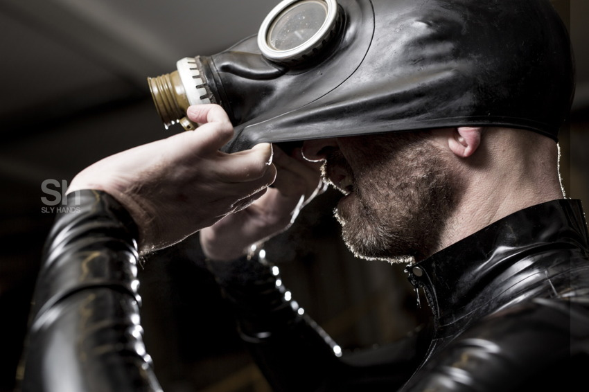 Man in rubber gear pulls rubber hood away from his face