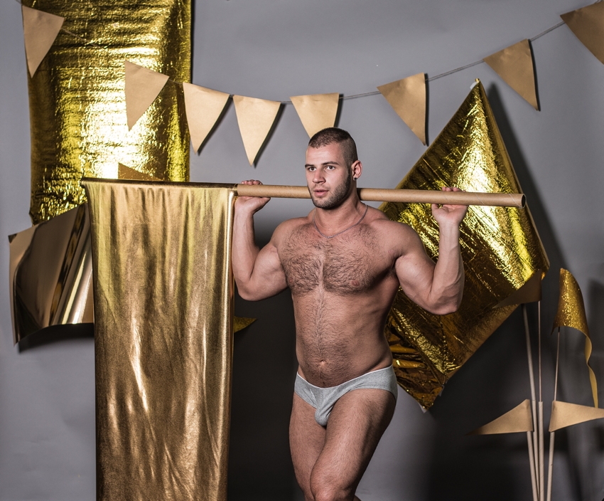 Lad in grey jockstrap holds gold-lamé flag on pole across shoulders, with other such flags in background