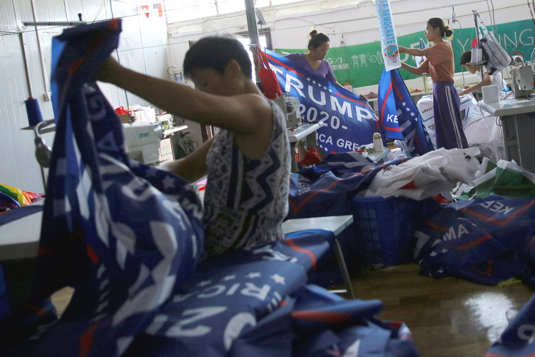 Sweatshop workers assemble TRUMP 2020 banners typeset in Arial