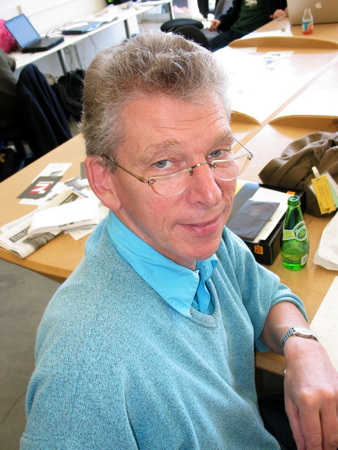 Bemused-looking man in blue sweater, glasses low on nose, regards us over his shoulder