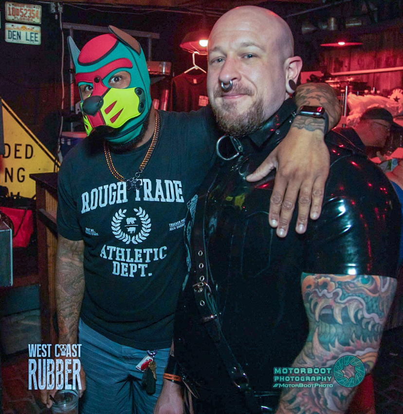 Black dude in garish pup hood has arm around stocky guy with nose ring and rubber shirting