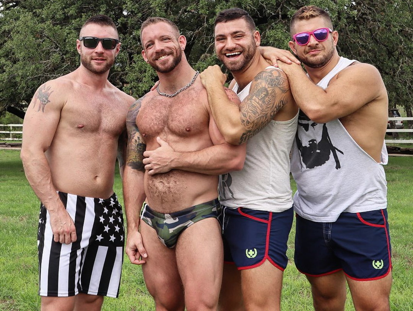 Slim, muscular, hairy-chested male in camo Speedo plus three friends in board shorts