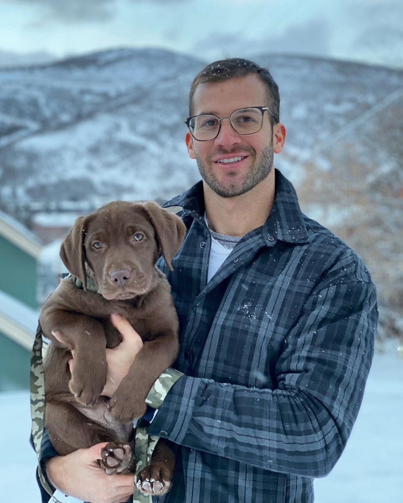 Handsome lad in glasses holds Labrador-retriever puppy, snow-dappled mountains in background
