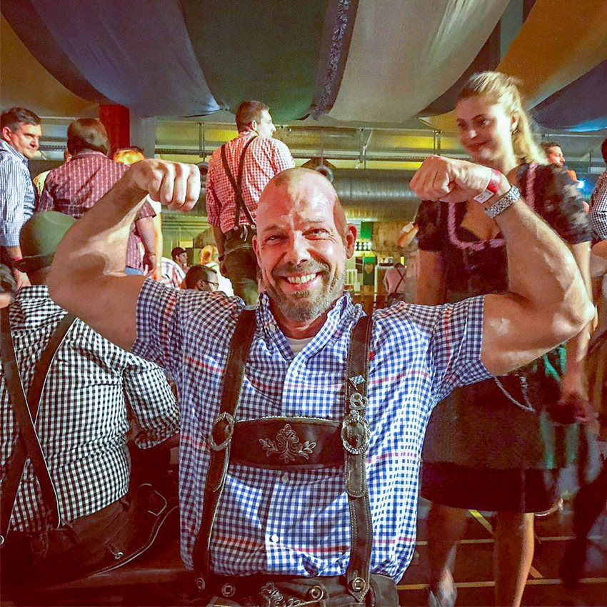 Muscular male in dirndl (or whatever the hell it is) does double biceps at Oktoberfest