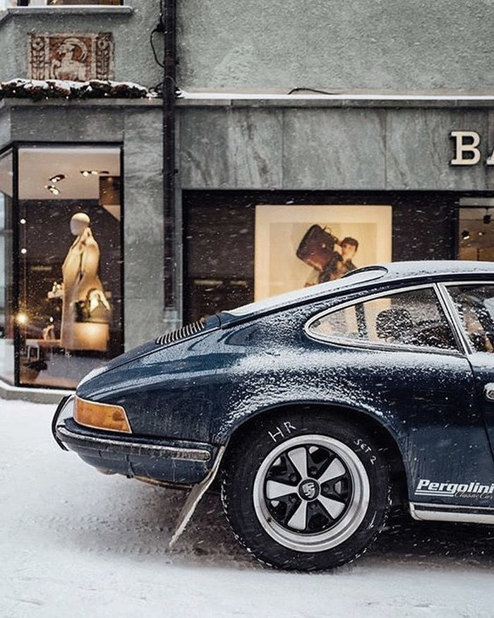 Side view of tail end of navy-blue 911 in light snow alongside fashionable shops